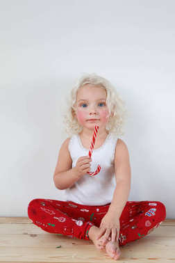 Portrait of rouge blonde adorable girl wears casual clothes or pyjamas, sits crossed legs, holds red and white caramel cane, isolated over white background. Beautiful child enjoys sweet