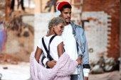 Smíšené rasy věří, že elegantní muž nosí sluchátka, obejme svou přítelkyni mulat, představují společně proti cihlové zdi s zamyšlený výraz, Užijte si volný čas. Americký pár v lásce.
