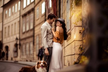 Happy stylish man strolls with dog, embraces his beautiful elegant girlfriend, have good relationship and feel true love, pose against ancient builduing background while walk on street together. stock vector