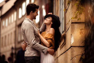 Passionate gorgeous young couple embrace each other while walk across ancient city. Cheerful elegant cute female model wears stylish hat, looks with cheerful expression in her boyfriend s eyes stock vector