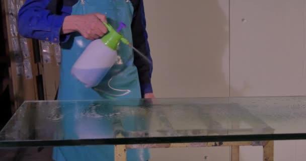 Pracovníka očistěte a osušte sklo na výrobu. S úsměvem poloviny dospělého pracovníka čisticí mýdlo sud na skleněné okno se stěrkou. Zaměstnance wash velká skleněná okna na stojanu. Použití vody pracovníka čisté sklo