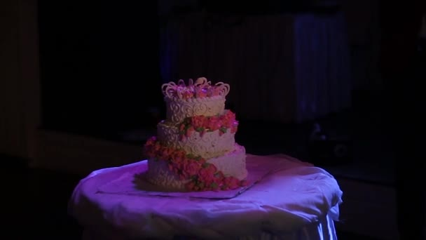 A multi level white wedding cake on a silver base and pink flowers on top. Veautiful wedding cake