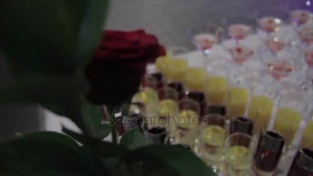 Champagne v brýlích s čerstvých cherry na stůl a strany pozadí. Pohled shora brýle s různých alkoholických nápojů na stůl na svatbě. Pyramida z červené modré šampaňské Martini sklenice na akci
