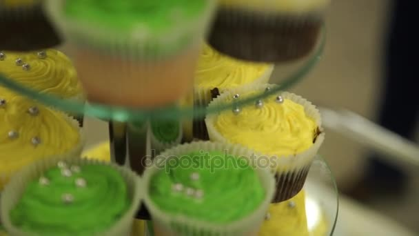 Cupcakes. Amazing chocolate cakes and cupcakes. Chocolate caramel cupcake with nuts and butterscotch syrup. Green and yellow cupcakes. Beautiful cupcakes with colored creams. Selective focus. Bokeh