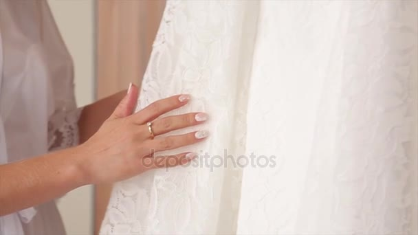Bílé svatební šaty na ramena, před obřad. Svatební šaty zblízka. Krásné svatební šaty pro nevěstu a barevné kytice. Velkou výhodou zbarvené květy. Detail banda růžičky. Svatební