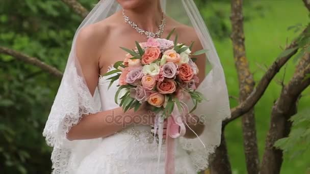 bride with flowers in hand outdoors. The bride is nervous before the wedding. Bride holding a perfume. nice wedding bouquet in brides hand. Bride is holding beautiful bright wedding bouquet. the
