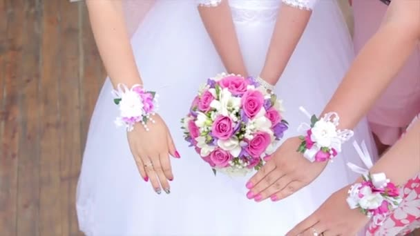 Bride and bridesmaids show bouquets of flowers. Bride and her girlfriends stand side by side and show the bouquets in their hands. Bride with flowers in hand outdoors. The bride is nervous before the