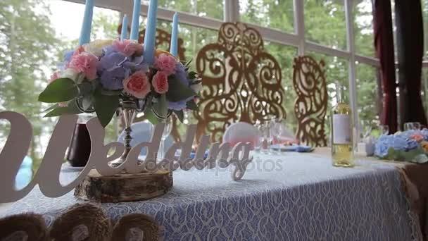 Svatební tabule na svatební hostině zdobené svatební kytice. Hodovní síň. sváteční stůl pro nevěstu a ženicha dekorované látkou a květinami. Tabulka pro nevěstu a ženicha. Svatba