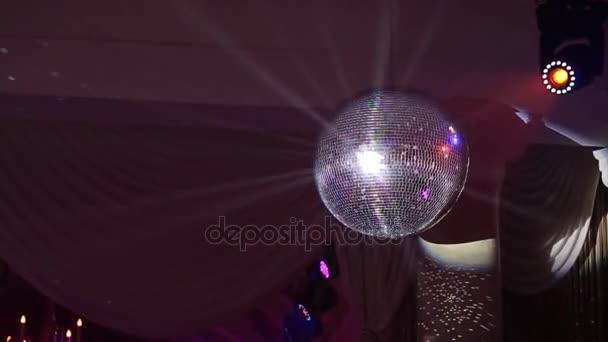 Fényes napsugarak, este fél háttér disco labdát. disco labdát lóg a mennyezetről ragyog a partin. Disco labdát