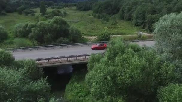 Letecký průzkum auta jezdí na hadí kmeny. Létání nad červený kabriolet jednotky na ulici. Letecký pohled na červené auto, které jede přes most. Provoz na mostě. Červené auto