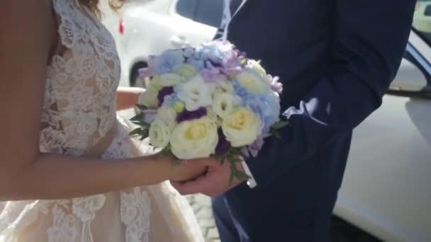 Braut und Bräutigam halten bunte Hochzeit Bouquet. Ehe-Konzept. Schöne junge Hochzeitspaar draußen in der Natur. Brautpaar mit dem stilvollen bouquet