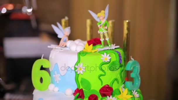 Green cake for birthday with fairies. Big celebration cake. Birthday cake with candles