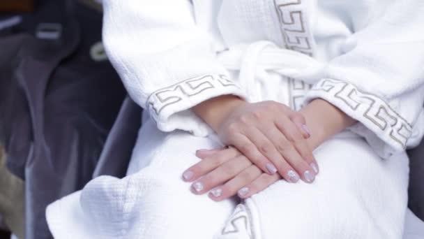 Die Braut sitzt auf einem Stuhl im weißen Kittel. Frau sitzt in ...