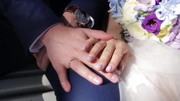 Újonnan házasodik jegygyűrű pár kezet. Menyasszony és a vőlegény a jegygyűrűt virág vagy esküvői csokor. Újonnan házasodik párok kezét eljegyzési gyürük