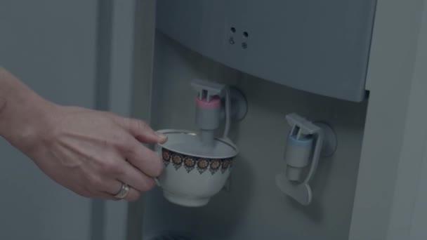 Női kéz, szolgálja a víz hidegebb, üveg csésze vizet. Ömlött a víz hidegebb. Ivóvíz minőségű vizet öntenek a hűvösebb. Office