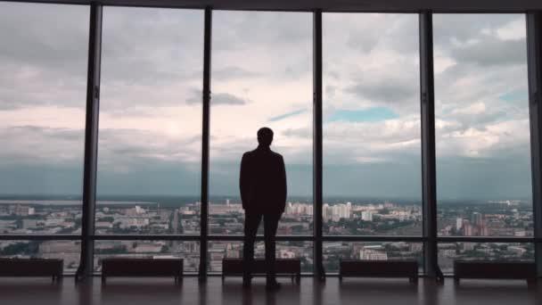 Az ember a hivatalos suites, aki álljon a városra panorámás ablak nézet hátulról. egy férfi áll szemben nagy panorámás wiindow nézet hátulról.