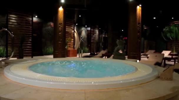 Relaxační bazén v lázních s vodopádem. Prázdná luxusní lázně s vířivkou a bazénem. Jacuzzi v sauně. Wellness