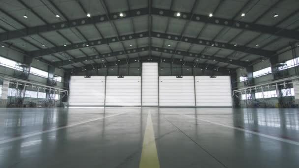 Garážová vrata závěrky a betonová podlaha uvnitř výrobní haly pro průmyslové pozadí. Letadlo v přední poloviny otevřel dveře do hangáru. Otevřené dveře hangáru. Mechanik, otevírání dveří