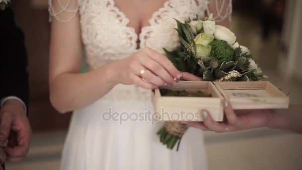 Closeup of a bride putting a gold wedding ring onto the grooms finger. wedding rings and hands of bride and groom. young wedding couple at ceremony. bride wear ring on grooms finger.