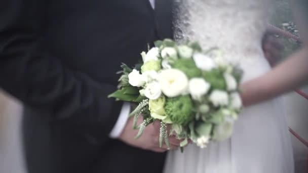Bride and groom holding colourful wedding bouquet. Marriage concept. Beautiful young wedding couple outside in nature. Wedding couple with the stylish bouquet