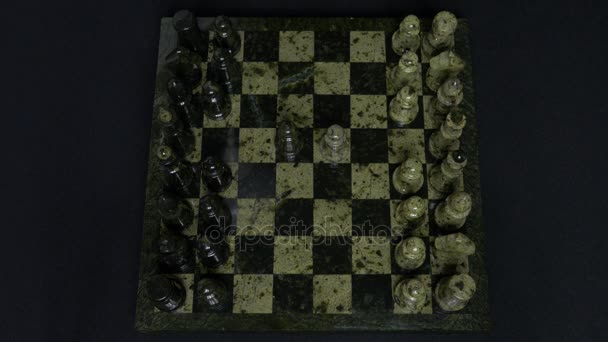 Checkmate. Start Of A Chess Game,the Figures Are Lined Up And A Person Makes The First Move. Hand moving a knight chess piece on chessboard. Mans hands play chess, checkmate in chess