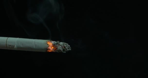 Hořící cigaretový kouř na černém pozadí. Cigaretu zapálil na černém pozadí. Cigareta spálil. Detailní záběr na cigaretu na popelník s krásný obláček kouře
