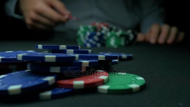 Primo piano di uomo che getta un Poker Chips al rallentatore. Primo piano della mano con gettoni da gioco di lancio su priorità bassa nera. Giocatore di poker, aumentando la sua posta in gioco gettando sul tavolo da gioco pedine