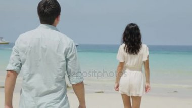 Cute couple in white clothing goes hand beach. Couple of teenagers running and flirting on the beach shore near the water. Woman walking on beach holidays holding hand of boyfriend following her