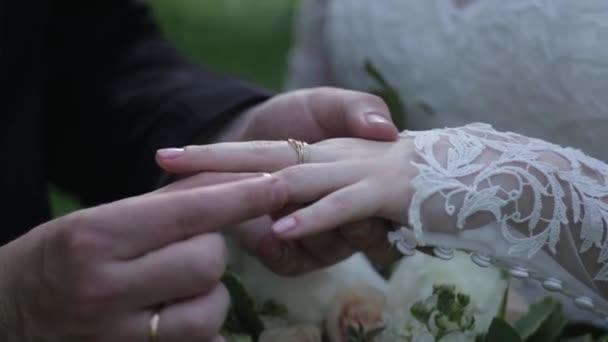 Sposa indossare anello sul dito degli sposi. Lo sposo mette lanello nuziale al dito della sposa. mani di matrimonio con gli anelli. Birde indossa lanello al dito dello sposo
