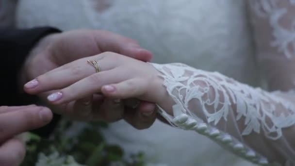 Bride wear ring on grooms finger. The groom puts the wedding ring to finger of the bride. marriage hands with rings. birde wears the ring on the finger of the groom