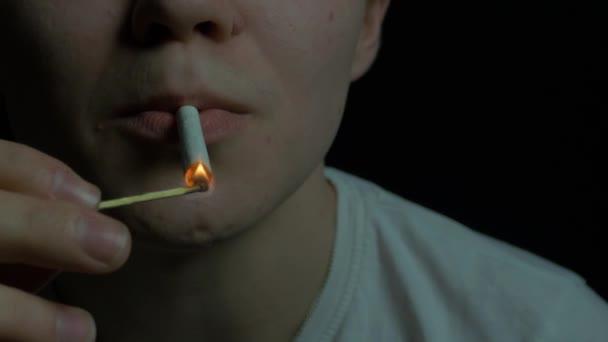 Mladý muž zapálí cigaretu sirkou. Portrét pohledný podnikatel s cigaretou na černém pozadí