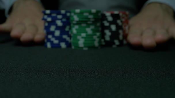 Fiches da poker e le mani sopra di esso sul tavolo verde. Blackjack in un casinò, un uomo fa una scommessa e mette un chip. Pila di fiches da poker e due mani sul tavolo verde.