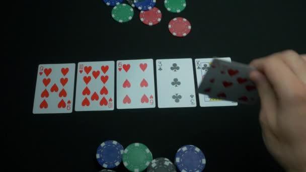 Mani di poker. Vista del primo piano di cinque carte che formano il poker tre di una mano gentile. Uomo che tiene le carte da poker su priorità bassa nera. Gioco dazzardo fiches e carte per il poker