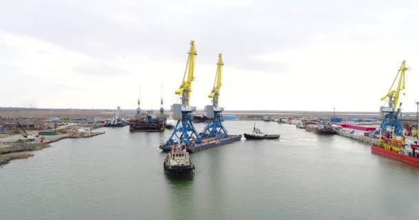 Vontató daruk tartályokhoz. Nagy konténerszállító hajó vontatóhajók húzzák. Felülről lefelé légifelvételek. Konténer rakomány áru hajón szállít-val működő daru híd hajógyár alkonyatkor a logisztikai importálása és exportálása