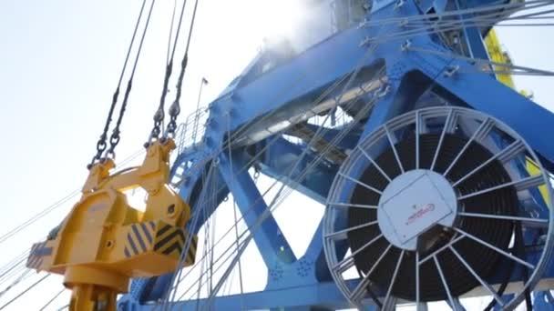 Luftverladung der Container per Kran, Handelshafen, Schifffahrt. Kräne zum Be-, Ent- und Sortieren von Containern. Containerfrachtschiff mit funktionierender Kranbrücke in der Dämmerung in der Werft für