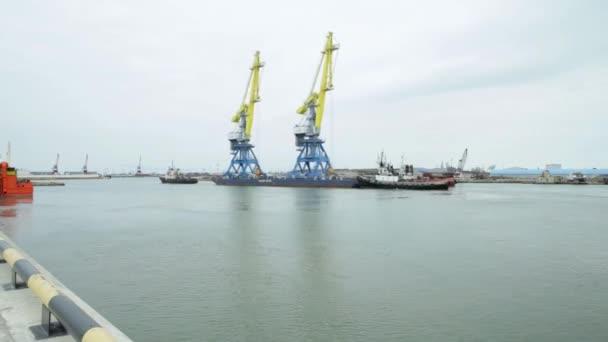 Vontató daruk a timelapse konténerek. Vontatóhajó segítő konténer hajó indulás után befejezett berakodás a kikötőben.