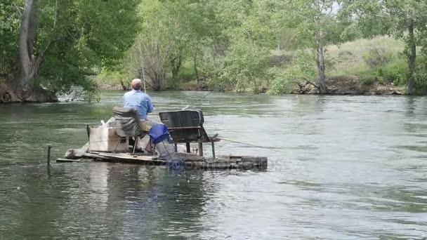Starší rybář rybolov v řece s rybářským prutem. Rybář je lov na řece