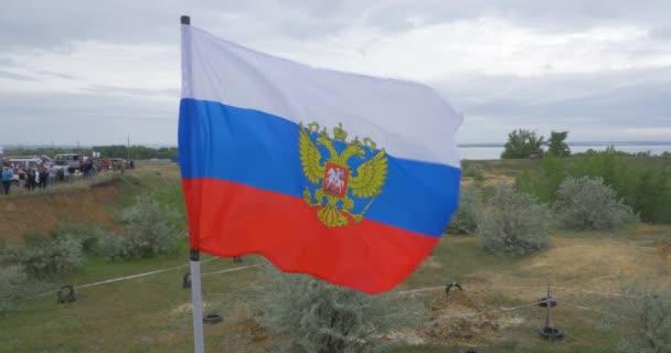 Az orosz zászló integetett a szél, a háttérben a hegyek és a természet. Oroszország hullámzó zászlaja. az orosz zászló természet háttér