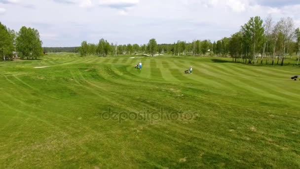 Letecký pohled na golfové hřiště. Golfisté kráčí plavební dráhy na kurzu s golfový bag a vozík