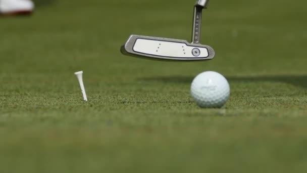 Profesionální golfista uvedení míče do díry. Golfový míček na okraji díry s hráčem v pozadí za slunečného dne