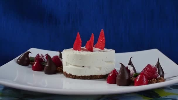 Torta fagyosan habcsók és a málna. Pavlova habcsók sütemények, friss málna és áfonya, sötét kék háttérrel. A lemez nagy habcsók zephyr