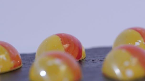 Barevné bonbóny zblízka. Sada barevných lízátka. Červené a žluté vánoční cukroví. Zpomalený pohyb