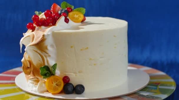 Tradiční vánoční ovocný koláč s bílou polevou a slazené ovoce. Smetanový dort s kumquat, brusinky, jahody