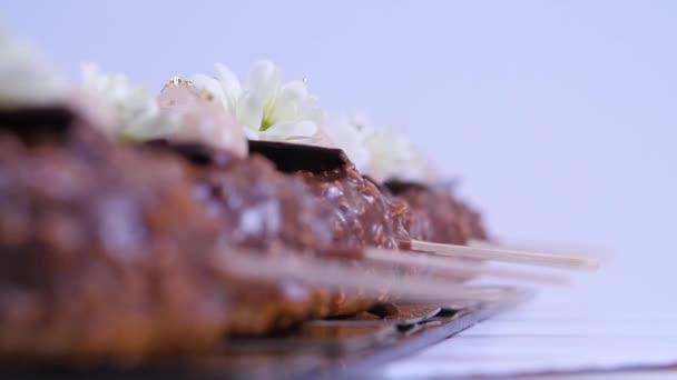 Zmrzlinu s čokoládou. Čokoládová zmrzlina na klacku. Čokoládové zmrzliny na tyčce zdobená květinami