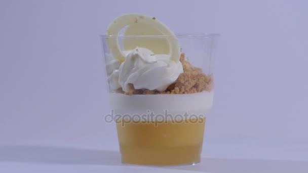 Sladký dezert ve skle s sušenku, šlehaný krém na bílém pozadí. Čerstvý moučník se smetanou a medem zblízka