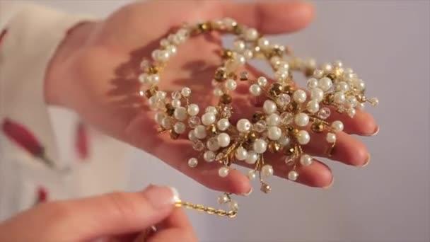 Nevěsty se drží ve svých rukou náhrdelník. Nevěsta drží v ruce krásný náhrdelník s diamantem
