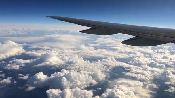 Křídlo letadla letícího nad mraky. Lidé dívají na oblohu z okna letadla, pomocí letecké dopravy k cestování