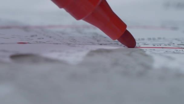 Vörös markerként írja egy papírlapra. Közelről. Tipp a marker. Vörös markerként árnyéka