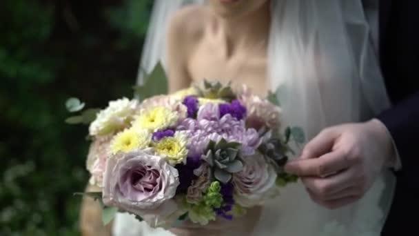 Szép esküvői csokor a menyasszony kezét. Kezében a menyasszony és a vőlegény egy gyönyörű menyasszonyi csokor gyűrűk
