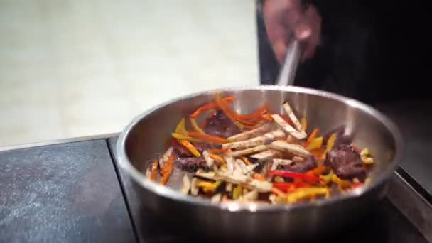 Chef putting vegetable to the pan for cooking vegetables. Chef is stirring vegetables in pan. Chef cooking vegetables in wok pan